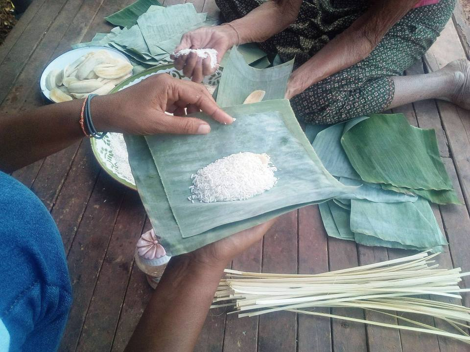 Uncooked rice-bananbeing wrapped- banana leaf