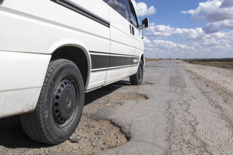 car on road potholes