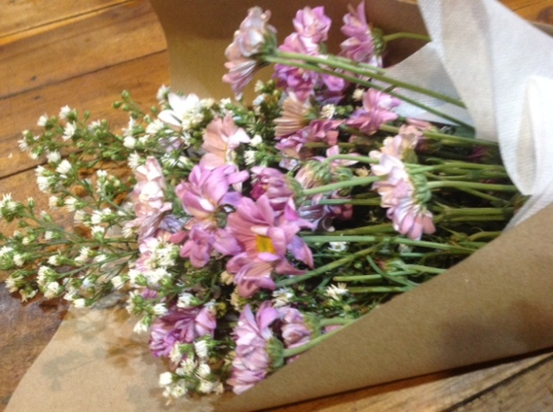 lilac and white flowers wrapped in brown paper