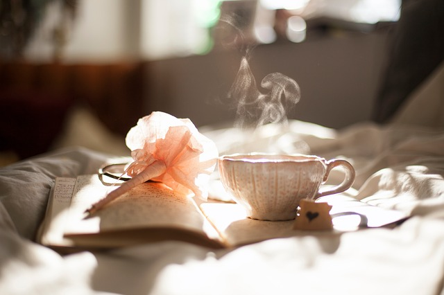 steaming tea in a cup a book and a flower