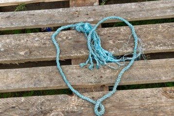 blue string heart shape on wooden pallet