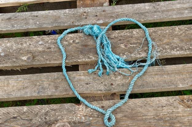 blue string heart shape on wooden pallet