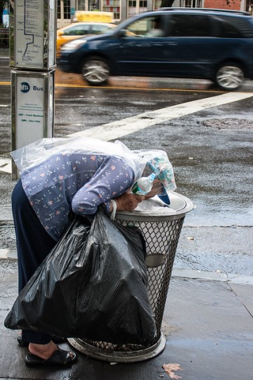 street lady going down a waste bin