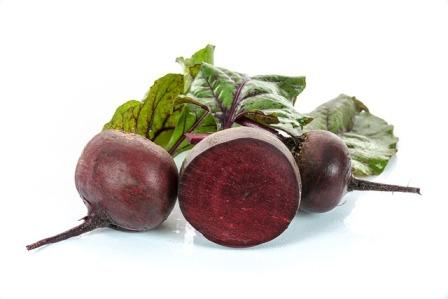 Red Beetroot with leaves and one cut beet